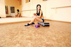 Young cheerful fit woman sitting on the step board at gym