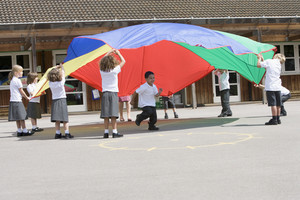 Young children playing with a parachute in a playground