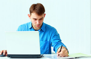Young concentrated businessman writing notes down with laptop at office