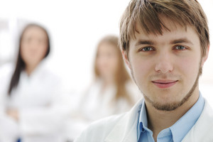 Young confident doctor in hospital lab, closeup face and his team behind him