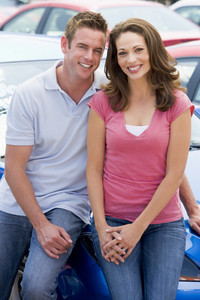 Young couple choosing new car on lot