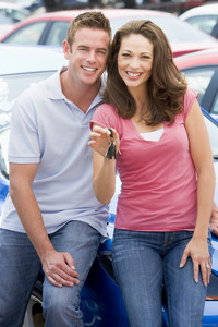 Young couple collecting new car from lot
