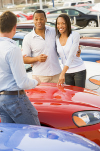 Young couple discussing new car with salesman on lot