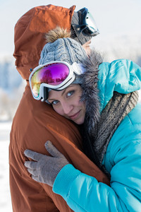 Young couple embracing in winter countryside ski goggles snow