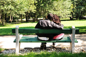 Young couple in love, sitting in nature on bench: lovers in park