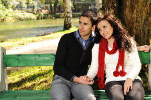 Young couple in nature sitting on bench, male and female together
