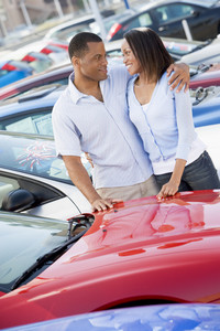 Young couple looking at new cars on lot