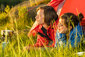 Young couple lying in tent enjoying sunset camping