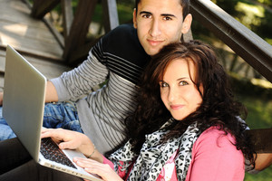Young couple, male and female sitting in park and studing and workind together with notebook and looking in camera