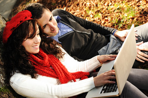 Young couple, male and female sitting in park and studing and workind together with notebook , fall period
