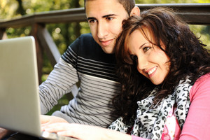 Young couple, male and female sitting in park and studing and workind together with notebook (laptop)