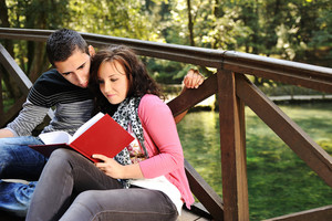 Young couple, male and female sitting in park beside the green river and reading a book