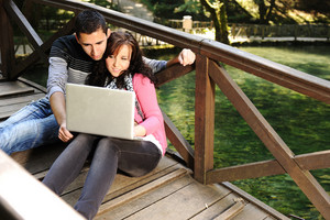 Young couple, male and female sitting in park beside the green river and studing and workind together with notebook (laptop)