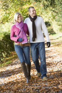 Young couple on autumn walk through woods
