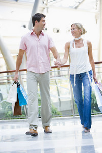 Young couple shopping in mall carrying bags