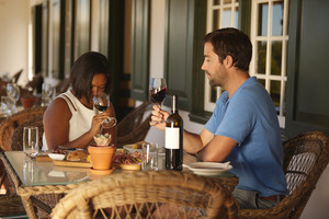 Young couple sitting at table tasting red wine at winery restaurant. Couple at wine tasting with woman smelling wine.