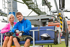 Young couple sitting on chair lift waiting for departing