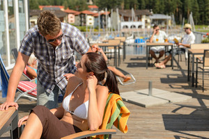 Young couple talking at bar beside beach summer terrace