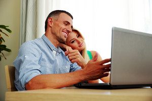 Young couple using laptop together at home