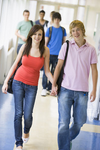 Young couple walking down university corridor