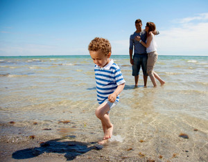 Young couple watches as their little son walks away from the water
