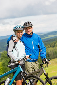 Young couple with mountain bikes enjoying fresh air and nature