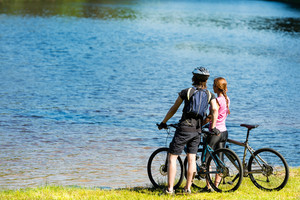 Young cyclist couple standing and watching the lake