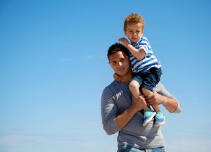 Young Dad Carries Cute Son Isolated in Blue