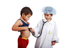 Young doctor in uniform examining little boy