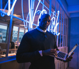Young executive standing in office with a laptop. Business executive in office with big neon light sign in the background