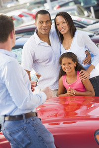 Young family collecting new car from salesman