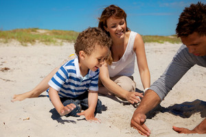 Young family enjoying the summer vacation on a sunny beach