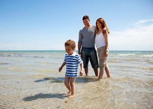 Young family enjoying the weekend on a sunny beach
