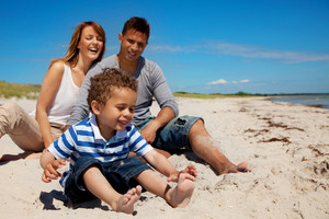 Young family enjoys their vacation on a bright sunny beach