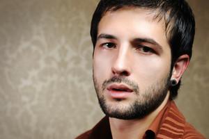 Young fashionable stylish man with a short beard posing