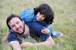 Young father and little cute girl, happiness on meadow