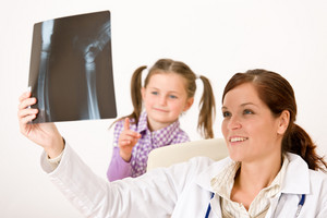 Young female doctor show x-ray to child at medical office