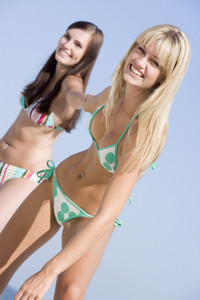 Young female friends on beach holiday wearing bikinis