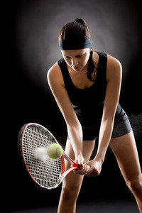 Young female tennis player ready to hit ball black background
