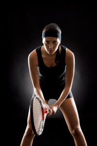 Young female tennis player ready to play on black background