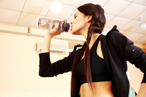 Young fit woman drinking water at gym
