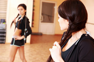 Young fit woman looking at her reflection in mirror at gym