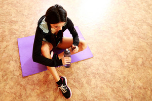 Young fit woman sitting on the yoga mat and holding bottle with water at gym