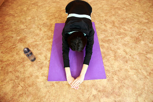 Young fit woman stretching on yoga mat at gym
