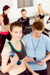 Young fitness woman doing spinning on bicycle with gym instructor