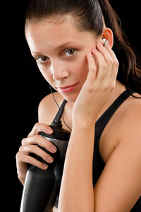 Young fitness woman with headphones and bottle on black background