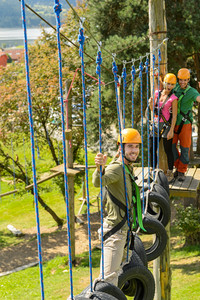 Young friends having fun in adventure park in helmets