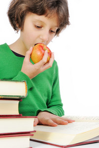 Young girl eating apple and studying