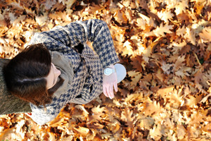Young girl in autumn park looking on watch