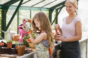 Young girl in greenhouse watering plant with woman holding pot smiling